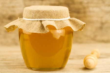 drizzler: glass jar of honey closed jute cloth drizzler on wooden background