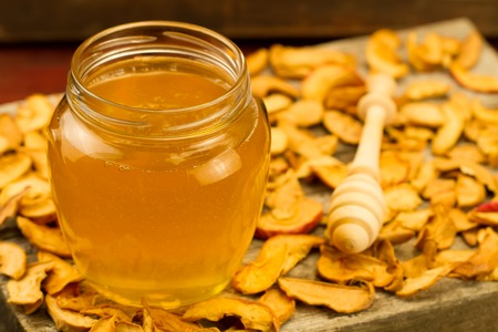 drizzler: glass jar of fresh honey with drizzler, with dried apples on wooden background