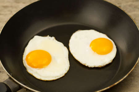 sunnyside: fried egg in a pan on wooden background