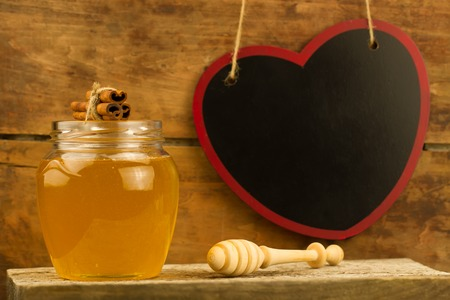 gold cans: glass jar of fresh honey with drizzler, cinnamon on wooden background