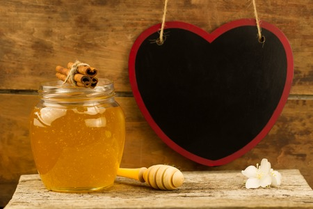 gold cans: glass jar of fresh honey with drizzler, cinnamon, flowers on wooden background