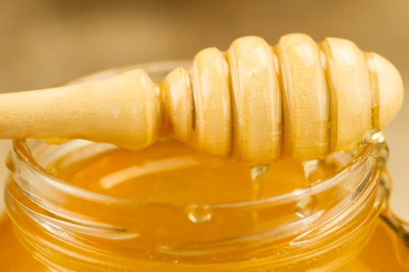 drizzler: glass jar of honey with drizzler on wooden background, macro Stock Photo