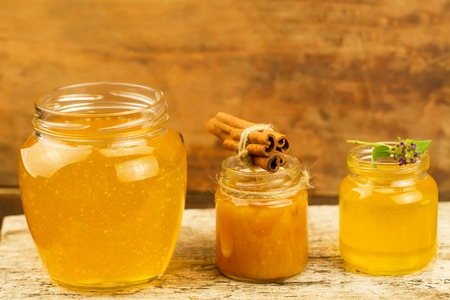 gold cans: three jars of honey with cinnamon, flowers on wooden background