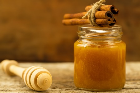 drizzler: small jar of honey with drizzler and cinnamon on wooden background