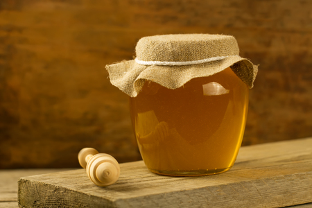 drizzler: glass jar of Linden honey with drizzler on wooden background