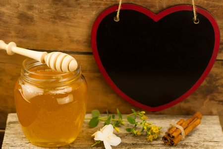 drizzler: glass jar of fresh honey with drizzler, cinnamon, flowers on wooden background