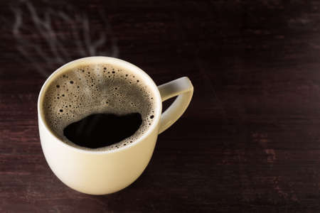 hot cup of freshly brewed black coffee on wooden table