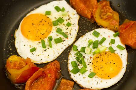 sunnyside: fried egg topped with onions and tomatoes on wooden background