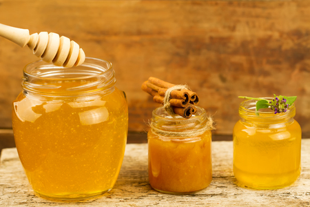 drizzler: three jars of honey with drizzler, cinnamon, flowers on wooden background Stock Photo