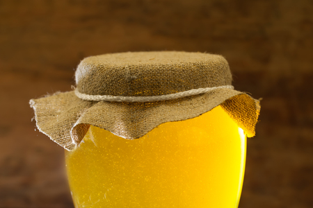 gold cans: glass jar of fresh honey on wooden background