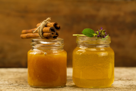 gold cans: two small jars of fresh honey with cinnamon and flowers on wooden background Stock Photo