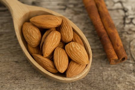 tidbit: peeled almonds in spoon on wooden background. For vegetarians