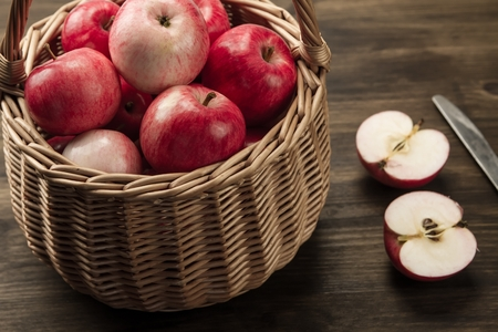 basket: Basket of fresh ripe red apples on wooden background