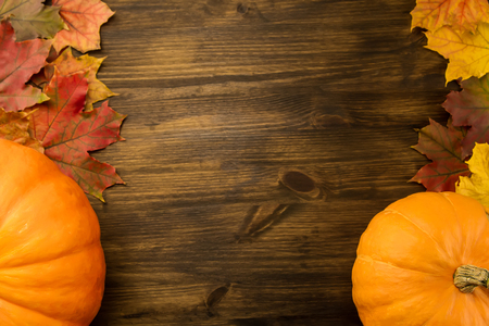 Yellow ripe pumpkin, maple leaves on wooden background