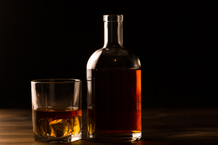 glass of whiskey with ice and a bottle on a wooden table