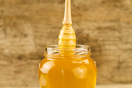 gold cans: glass jar of honey with drizzler on wooden background