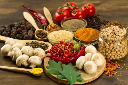epices: Table en bois avec des épices colorées, des herbes et des légumes Banque d'images