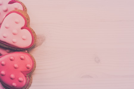day valentine: Delicious fresh cookies in the shape of a heart on a wooden background.