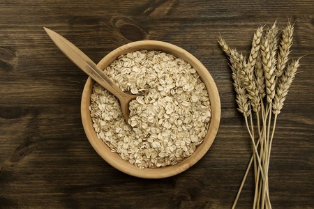 wheat: oatmeal flakes in a wooden bowl with a spoon, ears of wheat on the table