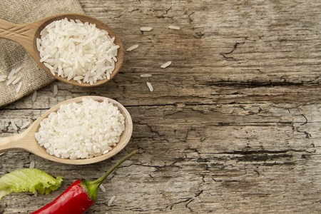healthy grains: different rice in spoons on wooden background. Healthy eating, diet, vegetarianism.