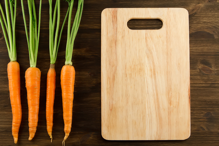 Bunch of fresh carrots with green leaves and cutting board on wooden background. Healthy vegetarian food