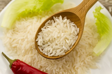 healthy grains: long grain rice in a wooden spoon on a background plate, green salad, chili pepper. Healthy eating, diet, vegetarianism. Stock Photo