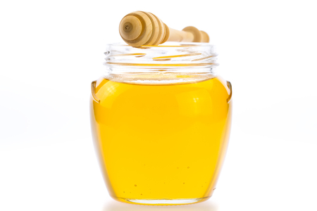 drizzler: glass jar of fresh honey with drizzler isolated on white background