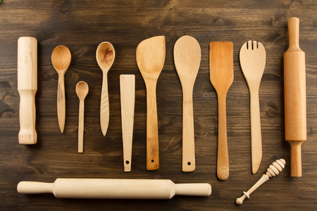 vintage kitchen: kitchen utensils on wooden background. spoon, mortar, kitchen spatula, rolling pin Stock Photo