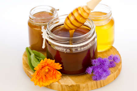 drizzler: glass jar of fresh honey with drizzler and flowers isolated on white background Stock Photo