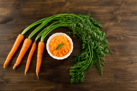Bunch of fresh carrots with green leaves on wooden . Cooking carrot salad. Healthy vegetarian food Standard-Bild