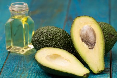 fresh avocados on wooden background. Healthy food, diet. Vegetarian. Avocado oil Standard-Bild