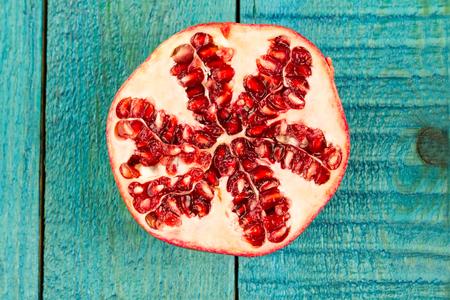 grenadine: Ripe pomegranate fruit on wooden vintage background. Healthy vegetarian food. Recipe, menu, mock up, cooking.
