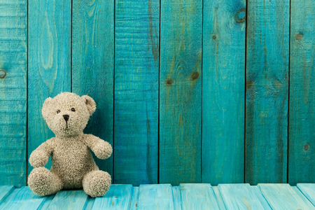 Teddy bear on turquoise wooden background. Baby toys Standard-Bild