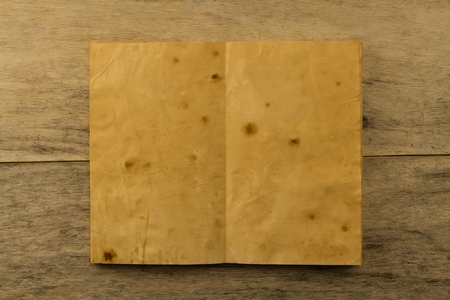 single story: open old vintage book on the aged wooden background. Two clean sheet of paper.