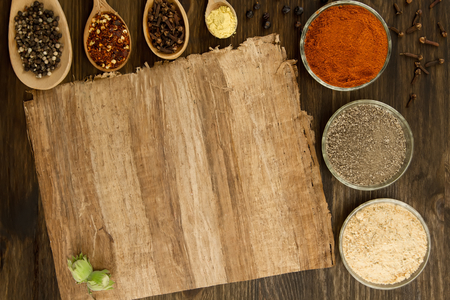 recipe background: sheet old vintage paper with spices on wooden background. Healthy vegetarian food. Recipe, menu, mock up, cooking.