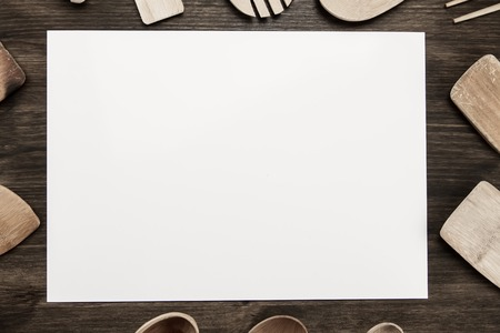 white sheet of paper with utensils on the old wooden background. Mock up