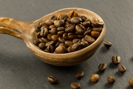fragrant coffee beans in a spoon on a black background