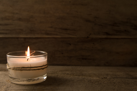 light  burning brightly candles on old wooden background. Spa, meditation, ritual, flavored. Standard-Bild