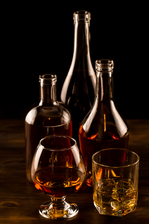 glass of whiskey with ice and a bottle on a wooden table. Cognac, brandy. Reklamní fotografie