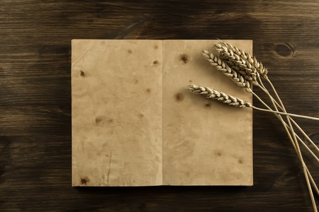 open old vintage book on the aged wooden background. ears of wheat. homemade, menu, recipe, mock up