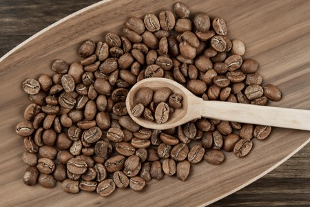 Roasted coffee beans on the plate on wooden background. Top view