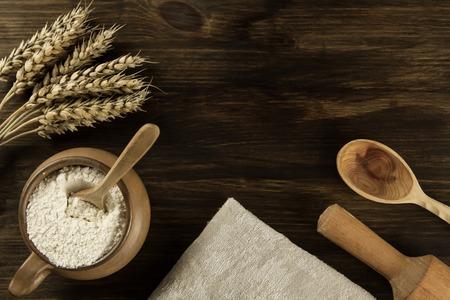 pot of flour, wheat ears, kitchen utensils on wooden background. homemade, menu, recipe, mock up Standard-Bild