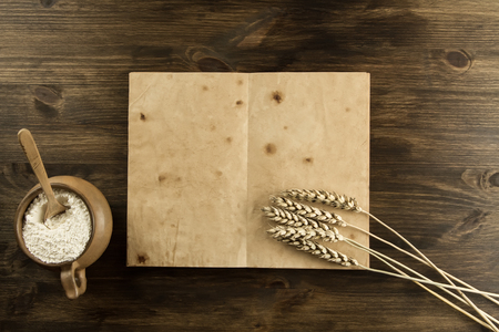 open old vintage book on the aged wooden background. Kitchen utensils, ears of wheat, flour in a pot. homemade, menu, recipe, mock up Standard-Bild