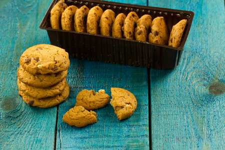 Chocolate chip cookies on an old vintage turquoise wooden background. Reklamní fotografie