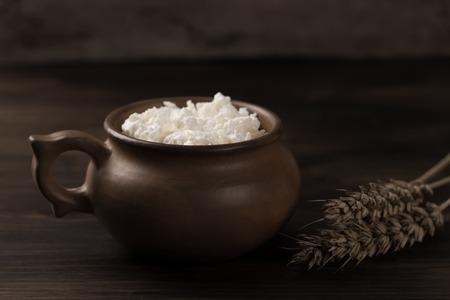fresh tasty curd in pot on wooden background. Homemade, cottage cheese Standard-Bild