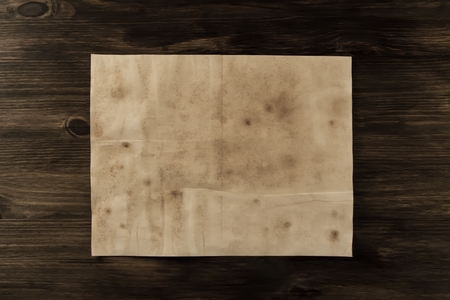 sheet old vintage paper on the aged wooden background. Parchment