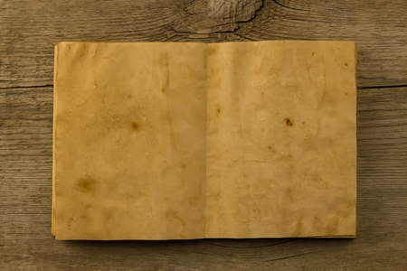 open old vintage book on the aged wooden background. Two clean sheet of paper.
