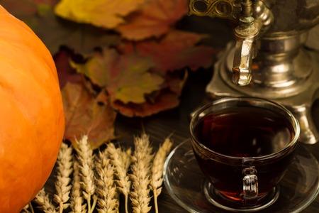 Tea still life with samovar, ripe orange pumpkins, maple leaves, wheat on wooden background. Thanksgiving, autumn. Standard-Bild