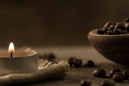 fragrant fried coffee beans. light  burning brightly candles on old wooden background. Standard-Bild