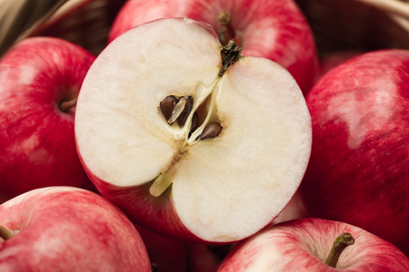 Basket of fresh ripe red apples on wooden background. Macro